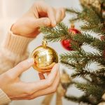 close up of woman decorating tree for christmas